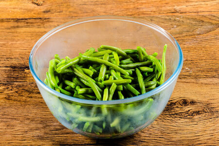 snap bean: common bean on glass cup on wooden table Stock Photo