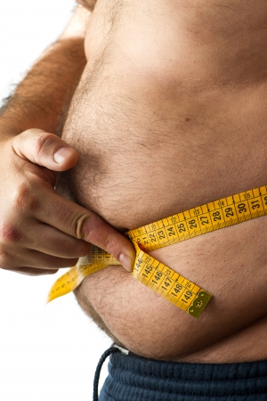 A man  measuring his belly fat photo