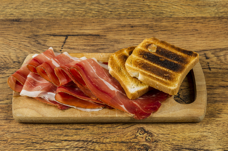 speck: european ham called speck on wooden board with bread slices