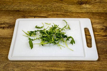 rocket lettuce: old  green salad on  plastic board