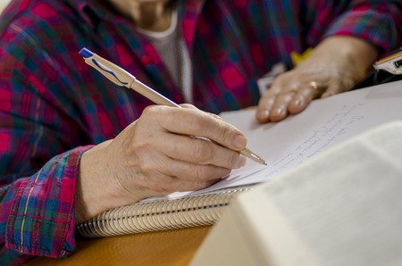 elderly woman sitting at a table writing