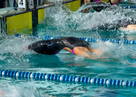 Female swimmer diving  into water at the start of a backstroke race  photo