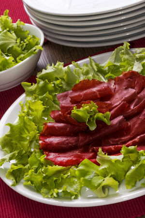 Italian meal called bresaola with green salad on white plate photo