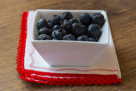 blueberries on white cup over an wooden table photo