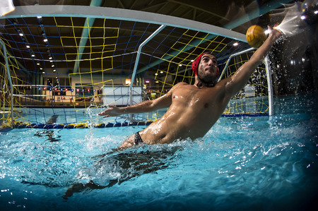 olympic game: A water polo goalkeeper and the ball going into the net of the goal.