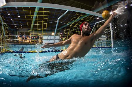 Un portero de waterpolo y la pelota entrar en la red de la meta. Editorial