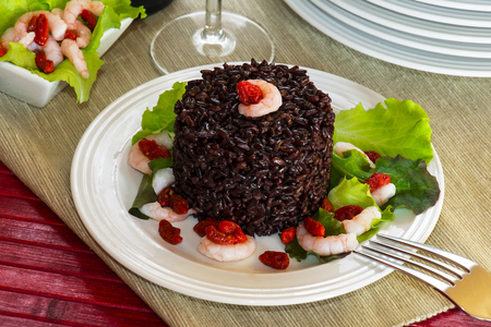 Black rice called Venere rice on white plate with shrimps and green sald photo