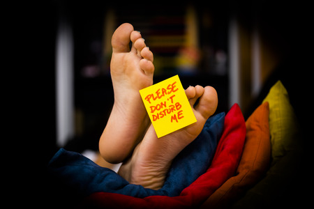 post card: Feet on the sofa with a post card and relax