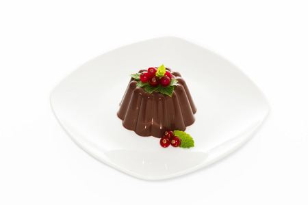 Chocolate pudding with red berries on white dish photo