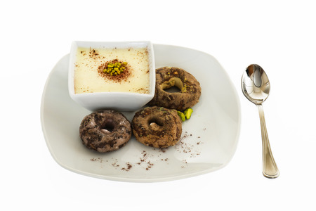 white chocolate dessert with pistachio and biscuits in white background photo