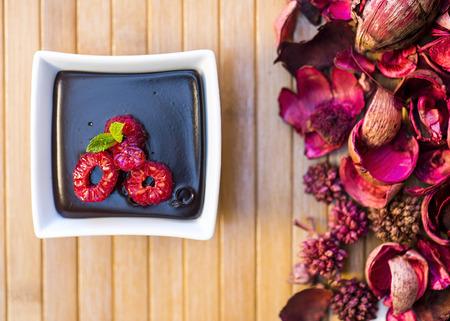 Chocolate dark Pudding with raspberries in gold light photo