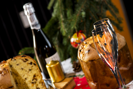 wine glasses and italian typical christmas cake called panettone on table wirh christmas tools Stock Photo