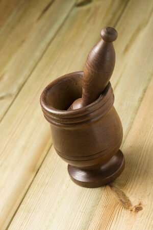 trituration: wooden mortar and pestle set on wooden board