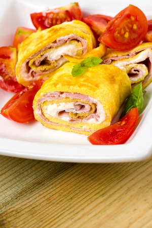 delicious rolls omelette with tomato, ham and cheese cream on wooden table ready for breakfast