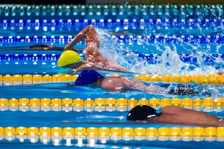 スイミング プールでフリー スタイルの男性の競争