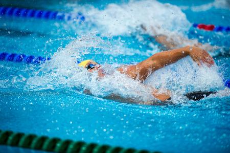 backstroke: backstroke swimmer during a race on swimming pool