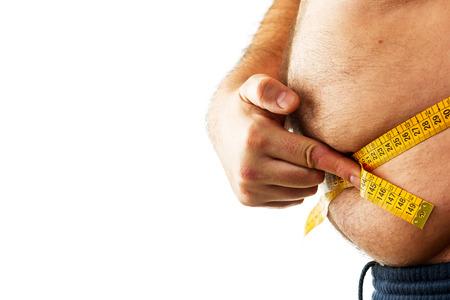 ombligo: hombre grande que mide su vientre con una cinta métrica en el fondo blanco Foto de archivo
