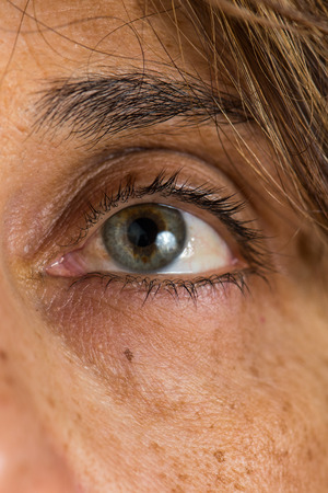 aging woman: Close up of a middle age  woman green eye and skin aging