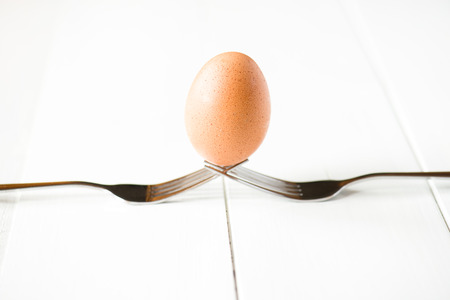 Balanced egg with fork on white background Stock fotó