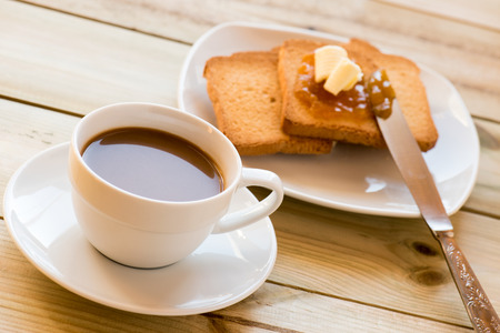 Breakfast time: cup of milky coffee, rusks with butter and orange jam on wooden table photo