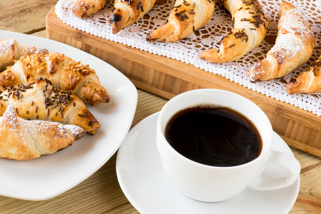 coffee cup with croissants on wooden table photo