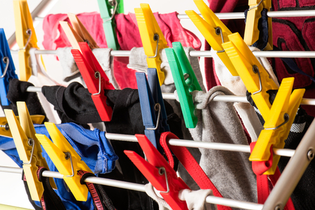 launder: mixed  clean laundry pinned with colourful clothespins on white background