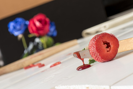 roses and blood: strawberry with a knife and juice drops on white wooden table and roses background Stock Photo