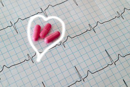 capsules and  cardiogram heart background