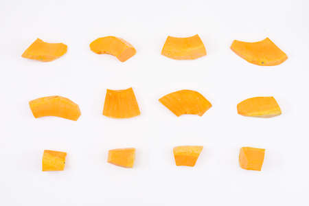 Peeled and chopped yellow pumpkin on white background