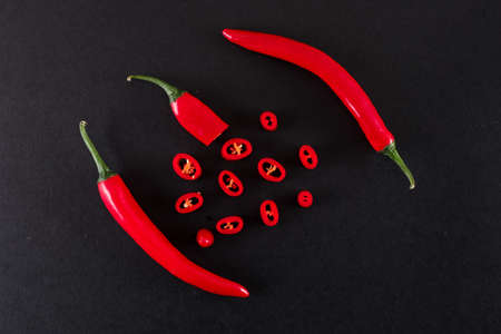 Full, bright, red chili peppers and sliced red hot chili peppers
