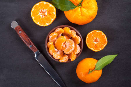 Top view mandarin in plate with knife