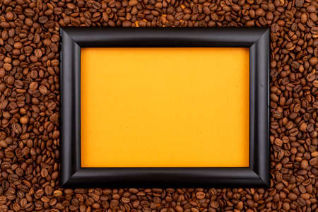 Black frame surrounded roasted coffee beans