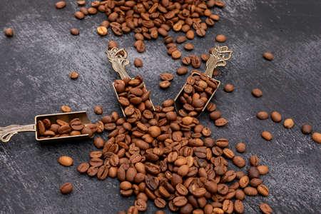 Kaffeebohnen im Metalllöffel auf dunklem Hintergrund Standard-Bild