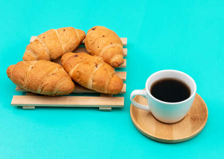 Side view of croissants with coffee on blue background horizontal