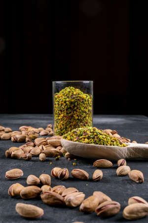 Side view full of glass cleaned pistachios with wooden spoon on dark stone and black background. vertical space for text