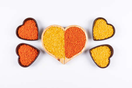 Some of yellow and red lentils with mini heart shaped bowls in a big heart shaped plate on white background, top view.