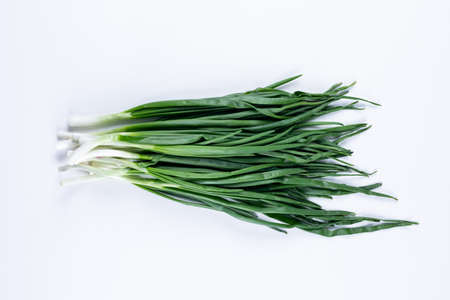 Fresh green spring onions or scallions flat lay on a white background
