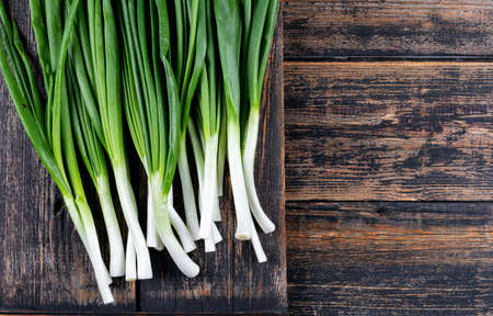 Fresh green spring onions or scallions on a dark wooden background. top view.  Banco de Imagens