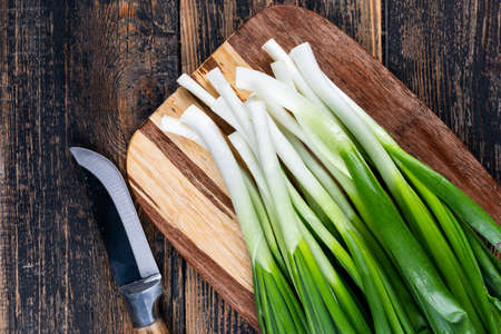 Top view spring onions or scallions on cutting board with knife on dark wooden background. horizontal