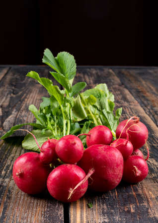 Side view fresh red radishes with fresh leafs on black and wooden background. horizontal