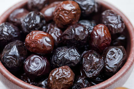Black and kalamata olives in a clay bowl on a white background. close-up.