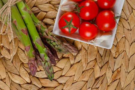 Bunch of raw asparagus with tomatoes and garlic in plate high angle view on a wicker placemat background