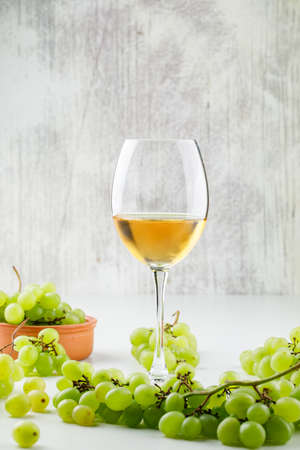 Green grapes with wine in goblet in a clay plate on white and grungy background, side view.