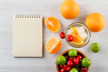 Oranges with infused water, green plums, cherries, copybook top view on a wooden background