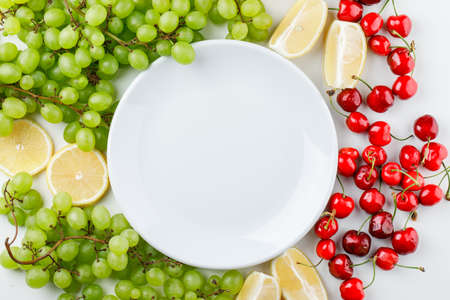 Green grapes with lemon slices, cherries, plate on white background, top view. Archivio Fotografico