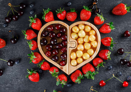 Cherries with strawberries, blueberries in a wooden plate on grey background, flat lay.