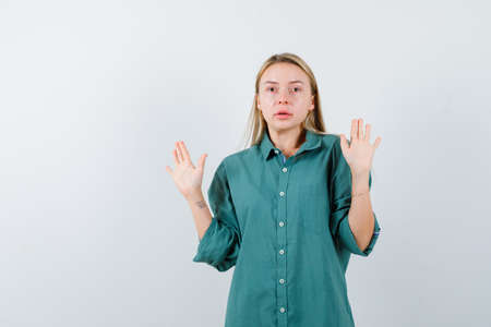 blonde woman in green shirt showing palms in surrender gesture and looking scared , front view.