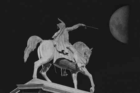 uomo a cavallo: La scultura di un cavaliere con una spada preparando per attaccare sotto la grande luna