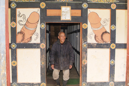 home decorated: Bhutan, man on entrance of his home, decorated with fertility symbol named lingam