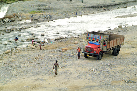 poorness: Assam, India - September 30th, 2007: Unidentified road workers and people on river bed by morning toilet in the small river on the border to Bhutan